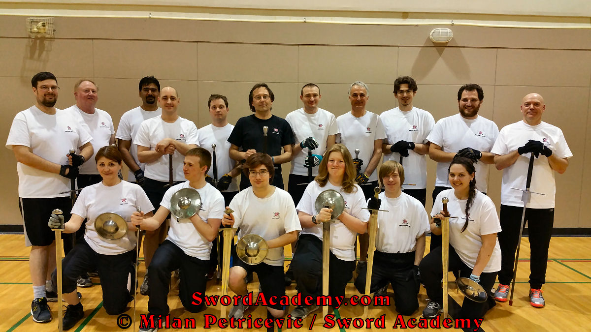 Sword Academy group photo with young students and ladies in first row with sword and buckler, students with two handed swords with instructor Milan Petricevic in the middle of the standing row proudly representing HEMA / WMA / Martial Arts.