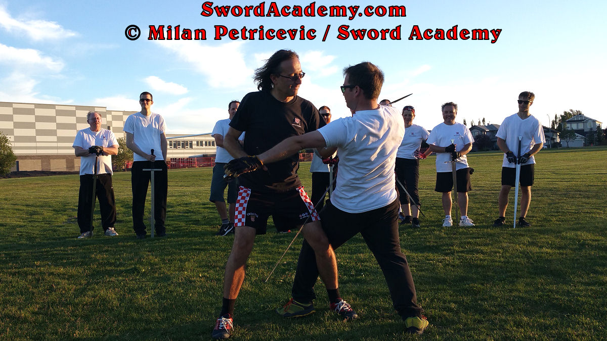 Milan demonstrates during an outdoor class in front of Sword Academy students armored sword exercise / drill using a throw aided by a weapon against the opponent as inspired by historical sources from the German medieval (and renaissance) tradition, part of Sword Academy HEMA / WMA / Martial Arts curriculum.