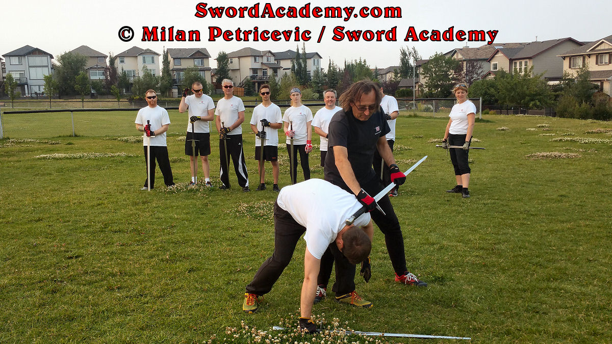 Milan demonstrates during an outdoor class in front of Sword Academy students armored sword exercise / drill using pommel to deliver a blow to the back of the opponent's head after execution of the partial disarm as inspired by historical sources from the German medieval (and renaissance) tradition, part of Sword Academy HEMA / WMA / Martial Arts curriculum.
