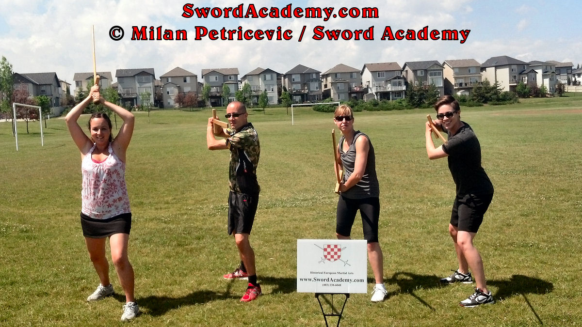 Students pose with longswords / swords at the end of the Introduction to Medieval Longsword course inspired by historical sources from German medieval (and renaissance) tradition, part of Sword Academy HEMA / WMA / Martial Arts curriculum.