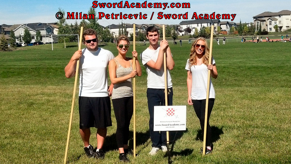 Students pose with staff weapons at the end of the Introduction to Renaissance Staff course inspired by historical sources from English renaissance tradition, part of Sword Academy HEMA / WMA / Martial Arts curriculum.