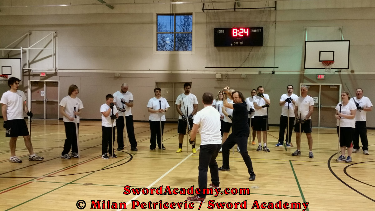 Milan demonstrates during an indoor class in front of Sword Academy students the longsword / sword exercise / drill using thrust from Ochs guard inspired by historical sources from the German medieval and renaissance tradition, part of Sword Academy HEMA / WMA / Martial Arts curriculum.