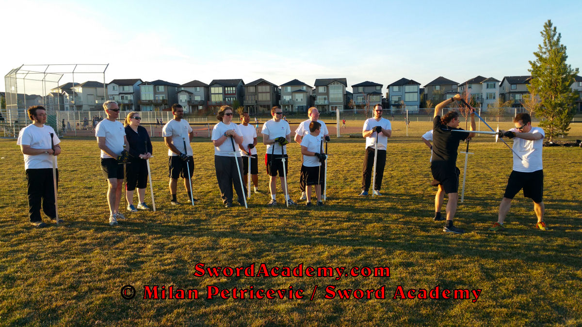 Milan demonstrates during an outdoor class in front of Sword Academy students the longsword / sword exercise / drill using Unterhau and thrust inspired by historical sources from the German medieval and renaissance tradition, part of Sword Academy HEMA / WMA / Martial Arts curriculum