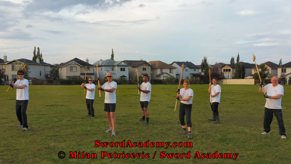 Sword Academy students in an outdoor class under Milan's supervision executes poleaxe solo / shadow training exercise / drill inspired by historical sources from the French and German medieval and renaissance tradition, part of Sword Academy HEMA / WMA / Martial Arts curriculum.