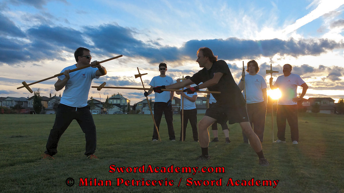 Milan demonstrates during an outdoor class in front of Sword Academy students and the setting sun poleaxe exercise / drill using dague to thrust in a composite attack inspired by historical sources from the French (and German) medieval (and renaissance) tradition, part of Sword Academy HEMA / WMA / Martial Arts curriculum.