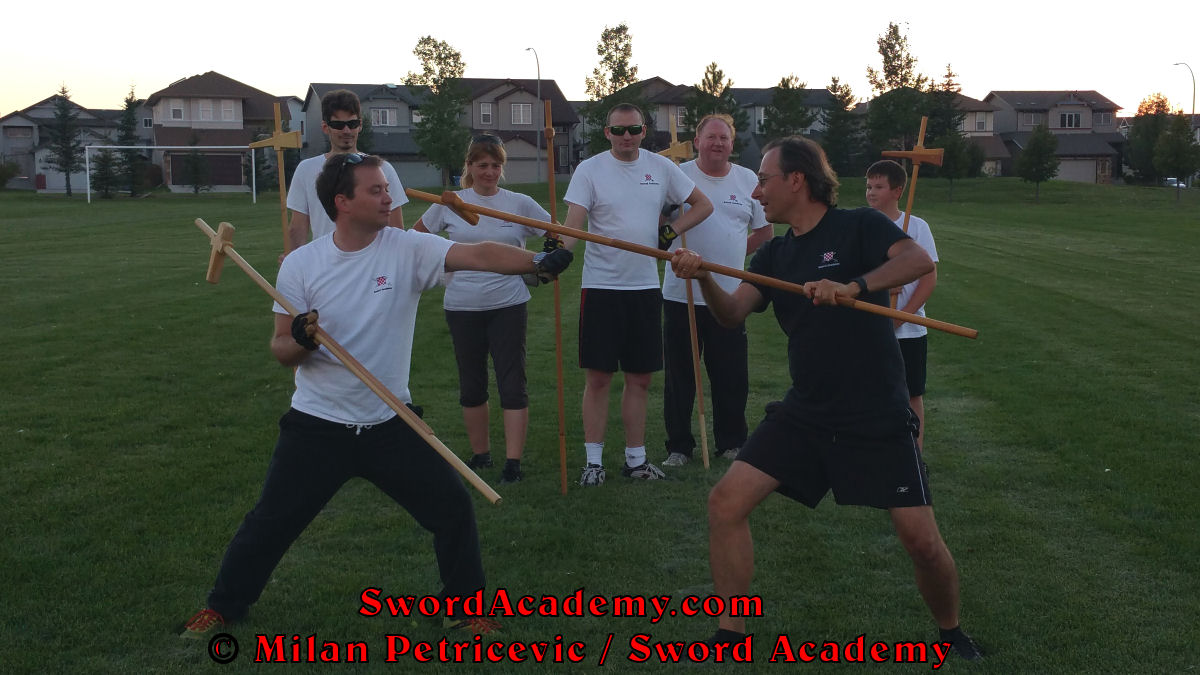 Milan demonstrates during an outdoor class in front of Sword Academy students poleaxe exercise / drill using queue to remove left hand from the shaft and following with the rising strike inspired by historical sources from the French (and German) medieval (and renaissance) tradition, part of Sword Academy HEMA / WMA / Martial Arts curriculum.