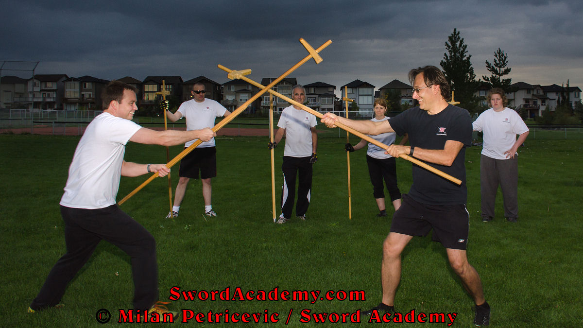 Milan demonstrates during an outdoor class in front of Sword Academy students and the stormy skies poleaxe / halberd exercise / drill as the weapons have crossed inspired by historical sources from the French (and German) medieval (and renaissance) tradition, part of Sword Academy HEMA / WMA / Martial Arts curriculum.