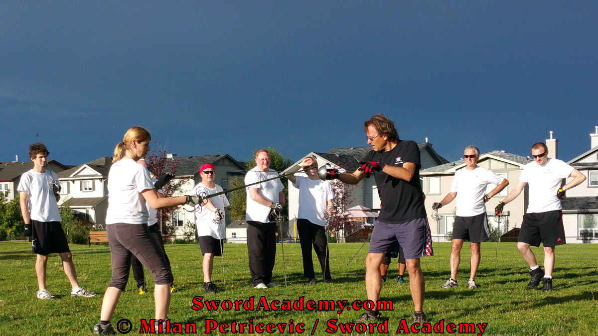 Milan demonstrates during an outdoor class with the stormy skies in background in front of Sword Academy students rapier exercise / drill using thrust from Quarta guard inspired by historical sources from the Italian renaissance tradition, part of Sword Academy HEMA / WMA / Martial Arts curriculum.