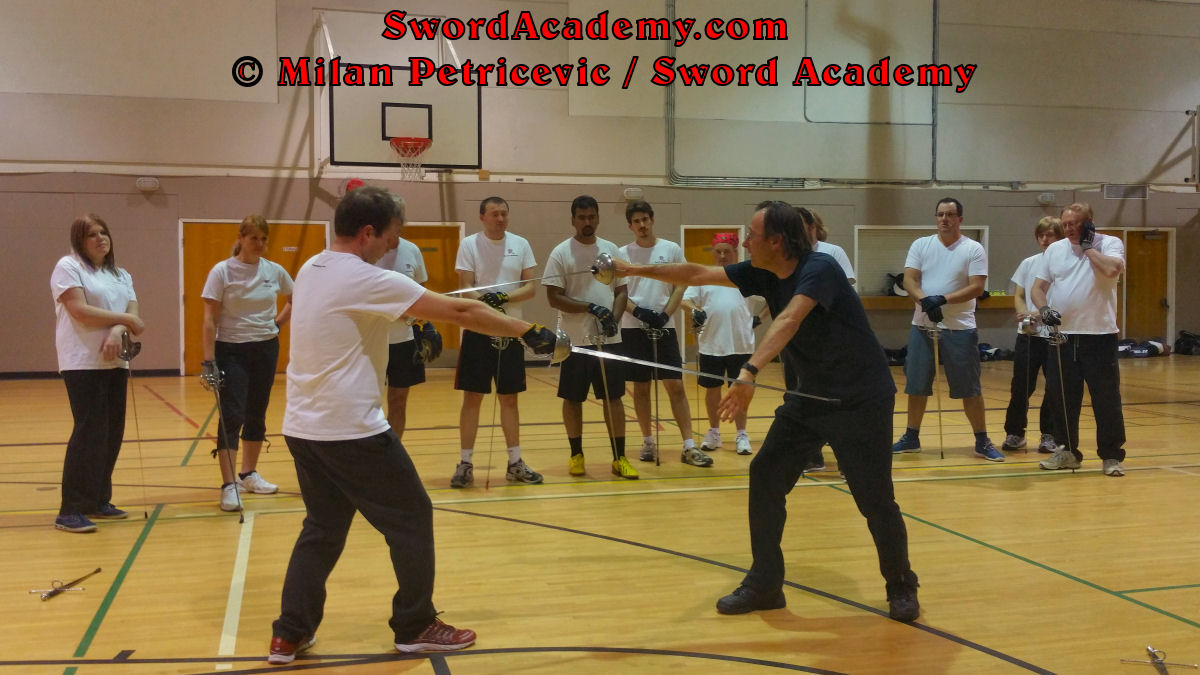 Milan demonstrates during an indoor class in front of Sword Academy students rapier exercise / drill using hand parry and thrust from Terza inspired by historical sources from the Italian renaissance tradition, part of Sword Academy HEMA / WMA / Martial Arts curriculum.