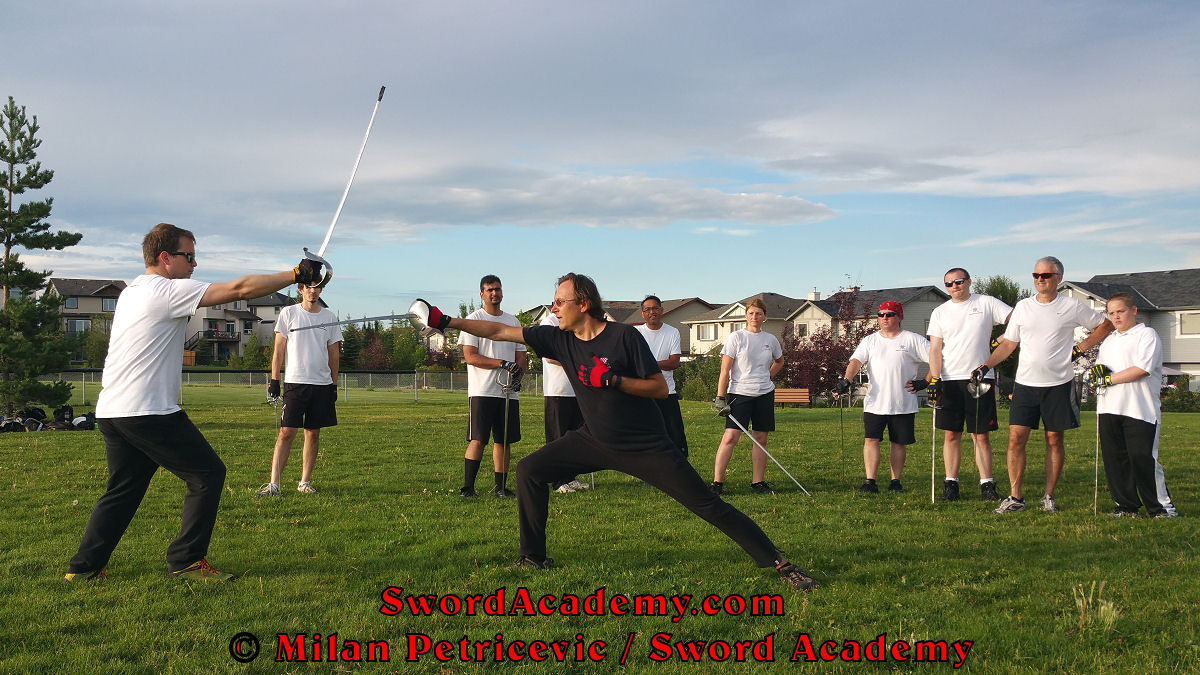 Milan demonstrates during an outdoor class in front of Sword Academy students sword / sabre exercise / drill using composite step lunge attack changing targets inspired by historical sources from the Croatian, Polish and English tradition, part of Sword Academy HEMA / WMA / Martial Arts curriculum.