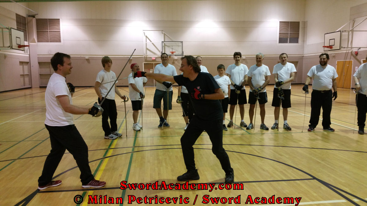 Milan demonstrates (and entertains) during an indoor class in front of Sword Academy students sword / sabre exercise / drill using composite attack changing from cuts into thrust inspired by historical sources from the Croatian, Polish and English tradition, part of Sword Academy HEMA / WMA / Martial Arts curriculum.