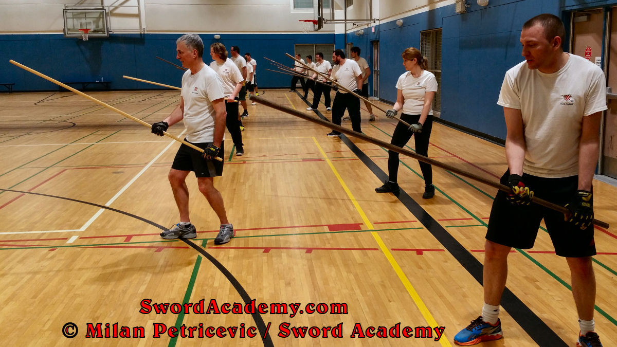 Sword Academy students practice footwork and elements of staff technique in a solo / shadow drill from the Low Guard during an indoor class inspired by historical sources from the English renaissance tradition, part of Sword Academy HEMA / WMA / Martial Arts curriculum.