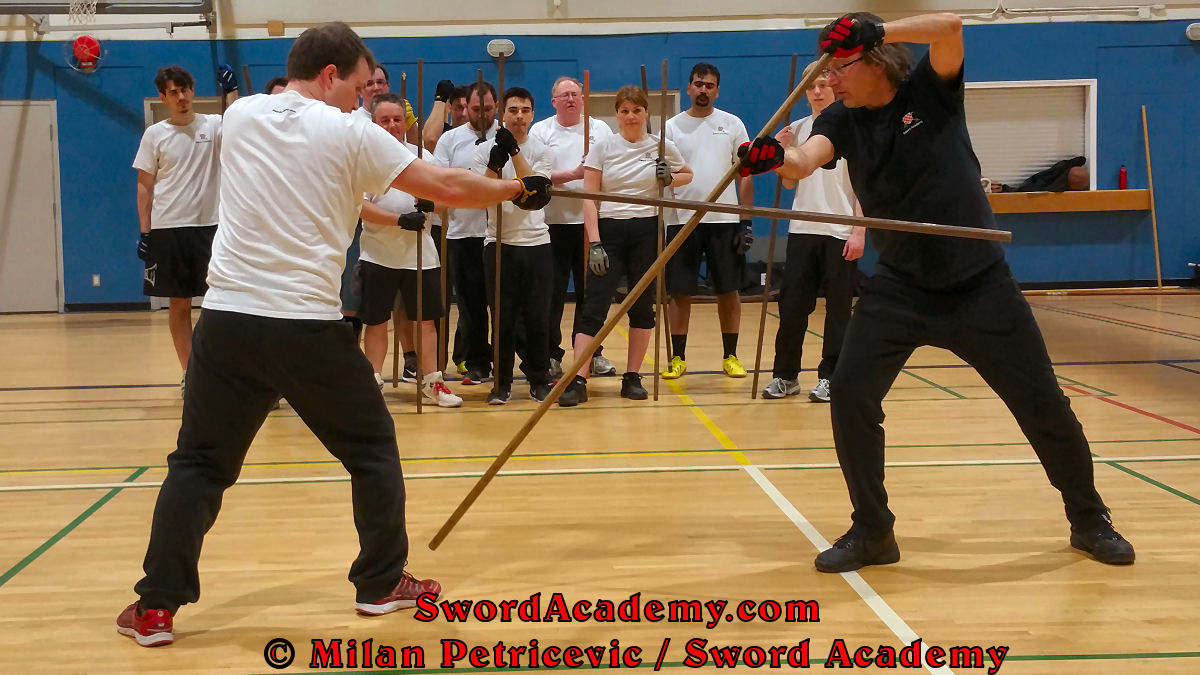 Milan demonstrates during an indoor class in front of Sword Academy students the staff exercise / drill using thrust to the foot after setting the opponent's thrust aside inspired by historical sources from the English renaissance tradition, part of Sword Academy HEMA / WMA / Martial Arts curriculum.