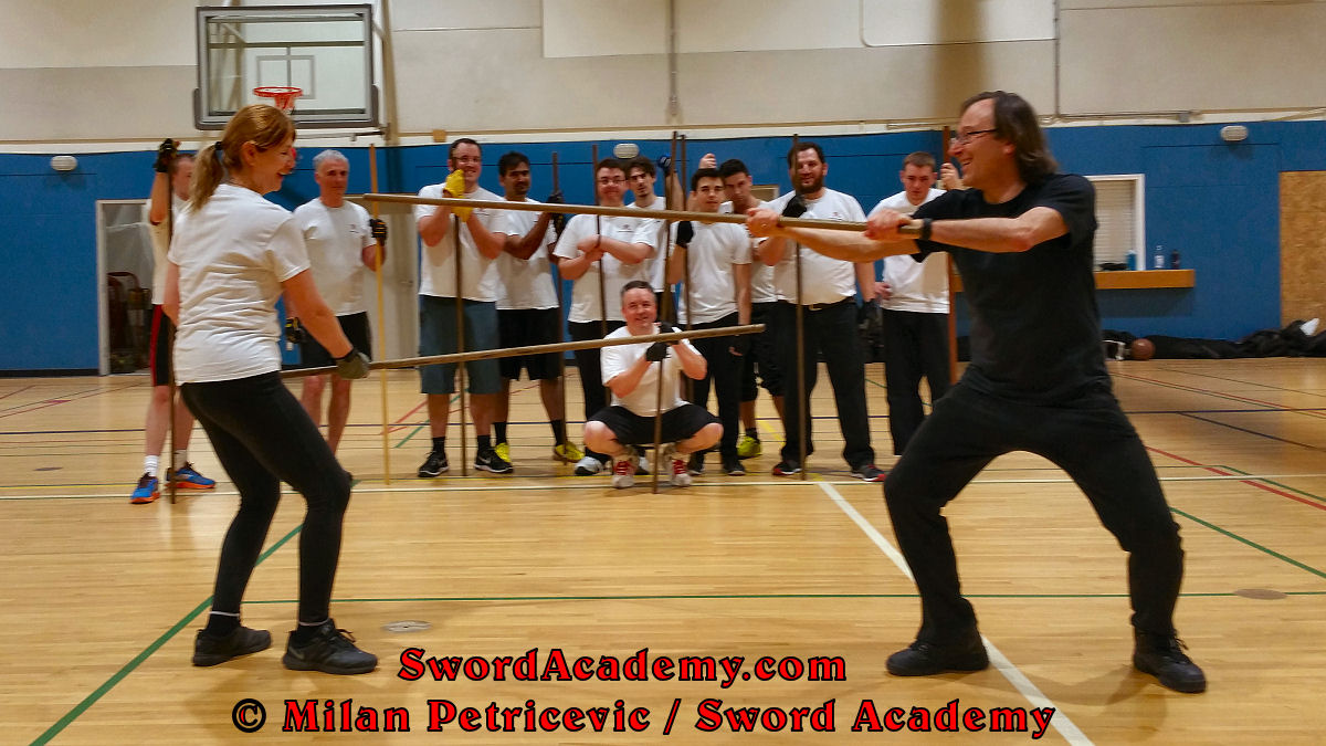 Milan demonstrates (and entertains) during an indoor class in front of Sword Academy students the staff exercise / drill using the rising forehand strike to the head inspired by historical sources from the English renaissance tradition, part of Sword Academy HEMA / WMA / Martial Arts curriculum.