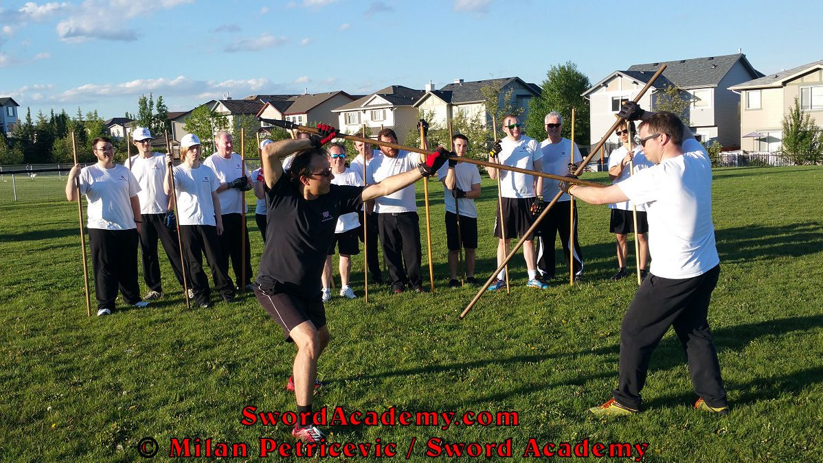 Milan demonstrates during an outdoor class in front of Sword Academy students the staff exercise / drill inspired by historical sources from the German renaissance tradition, part of Sword Academy HEMA / WMA / Martial Arts curriculum.