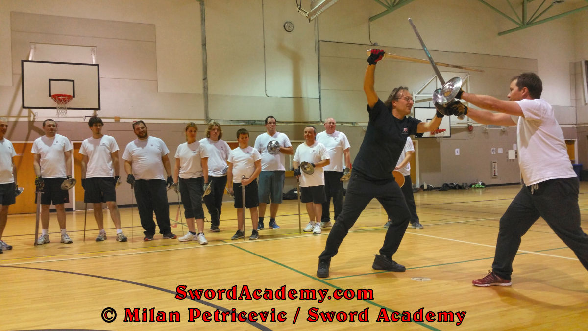 Milan demonstrates during an indoor class in front of Sword Academy students sword and buckler exercise / drill using followup descending thrust to the head from the bind inspired by historical sources from the German medieval and renaissance tradition, part of Sword Academy HEMA / WMA / Martial Arts curriculum.