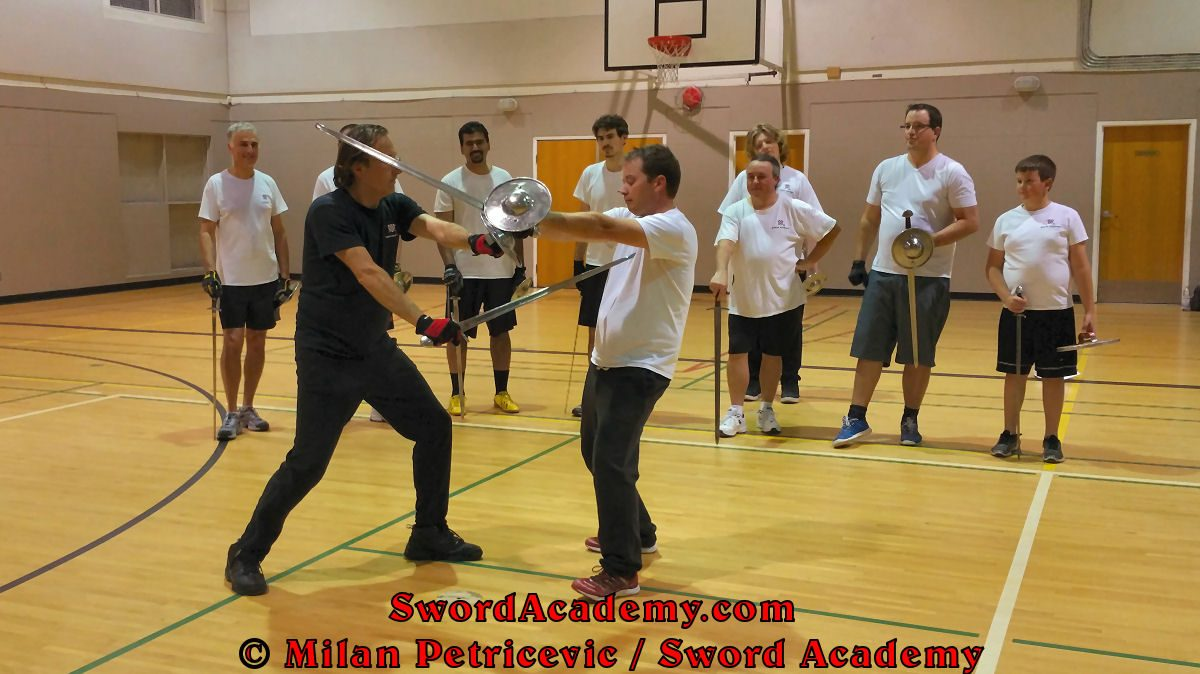 Milan demonstrates during an indoor class in front of Sword Academy students sword and buckler exercise / drill using followup rising thrust from the bind inspired by historical sources from the German medieval and renaissance tradition, part of Sword Academy HEMA / WMA / Martial Arts curriculum.