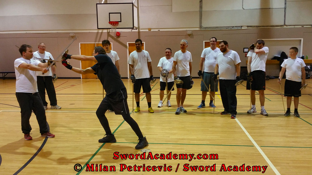 Milan demonstrates during an indoor class in front of Sword Academy students sword and buckler exercise / drill using a short edge cut from the weak side inspired by historical sources from the German medieval and renaissance tradition, part of Sword Academy HEMA / WMA / Martial Arts curriculum.