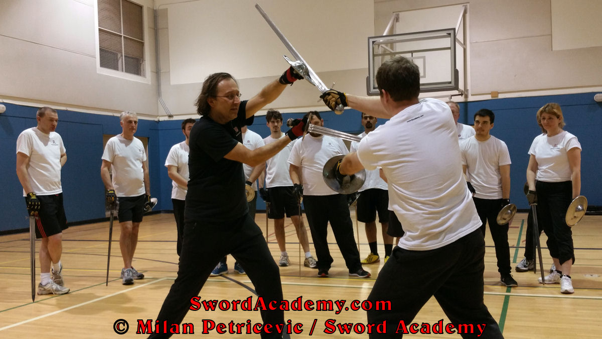 Milan demonstrates during an indoor class in front of Sword Academy students sword and buckler exercise / drill using a separation of sword and buckler to deliver a thrust inspired by historical sources from the German medieval and renaissance tradition, part of Sword Academy HEMA / WMA / Martial Arts curriculum.