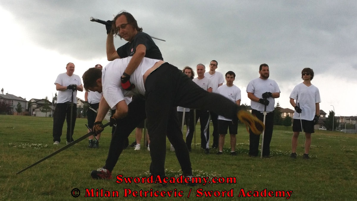 Milan demonstrates during an outdoor class in front of Sword Academy students wrestling applied to longwrord / sword exercise / drill using a Ringen Am Schwert throw against the charging opponent inspired by historical sources from the German medieval (and renaissance) tradition, part of Sword Academy HEMA / WMA / Martial Arts curriculum.