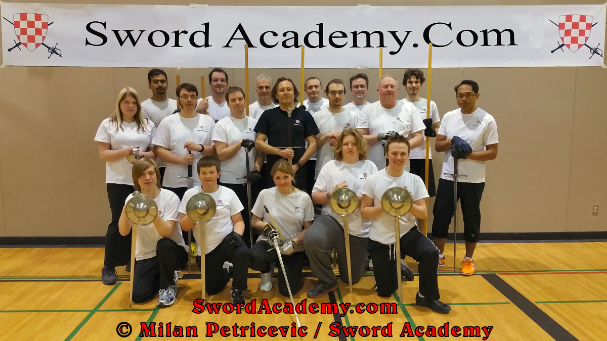 Sword Academy group photo with young students in first row with sword and buckler (and rapier), students with two handed swords with instructor Milan Petricevic in the middle of the first standing row, and students with staff in the back of the standing row proudly representing HEMA / WMA / Martial Arts.