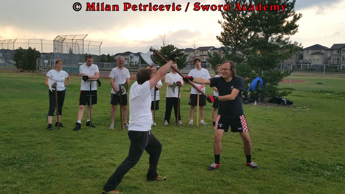 Milan demonstrates during an outdoor class in front of Sword Academy students two handed axe against the armored sword exercise overpowering the opponent with the momentum of the two handed axe as inspired by historical sources from the German medieval (and renaissance) tradition, part of Sword Academy HEMA / WMA / Martial Arts curriculum.
