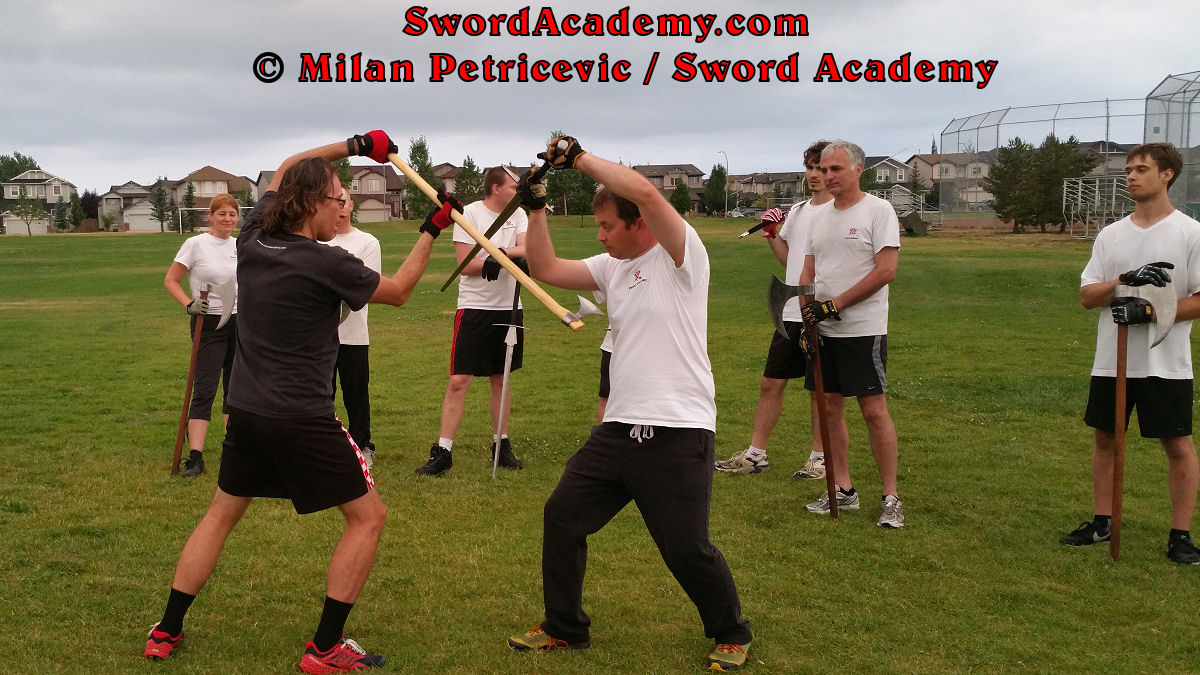 Milan demonstrates during an outdoor class in front of Sword Academy students two handed axe against the armored sword exercise switching attacks using the nimble two handed axe as inspired by historical sources from the German medieval (and renaissance) tradition, part of Sword Academy HEMA / WMA / Martial Arts curriculum.