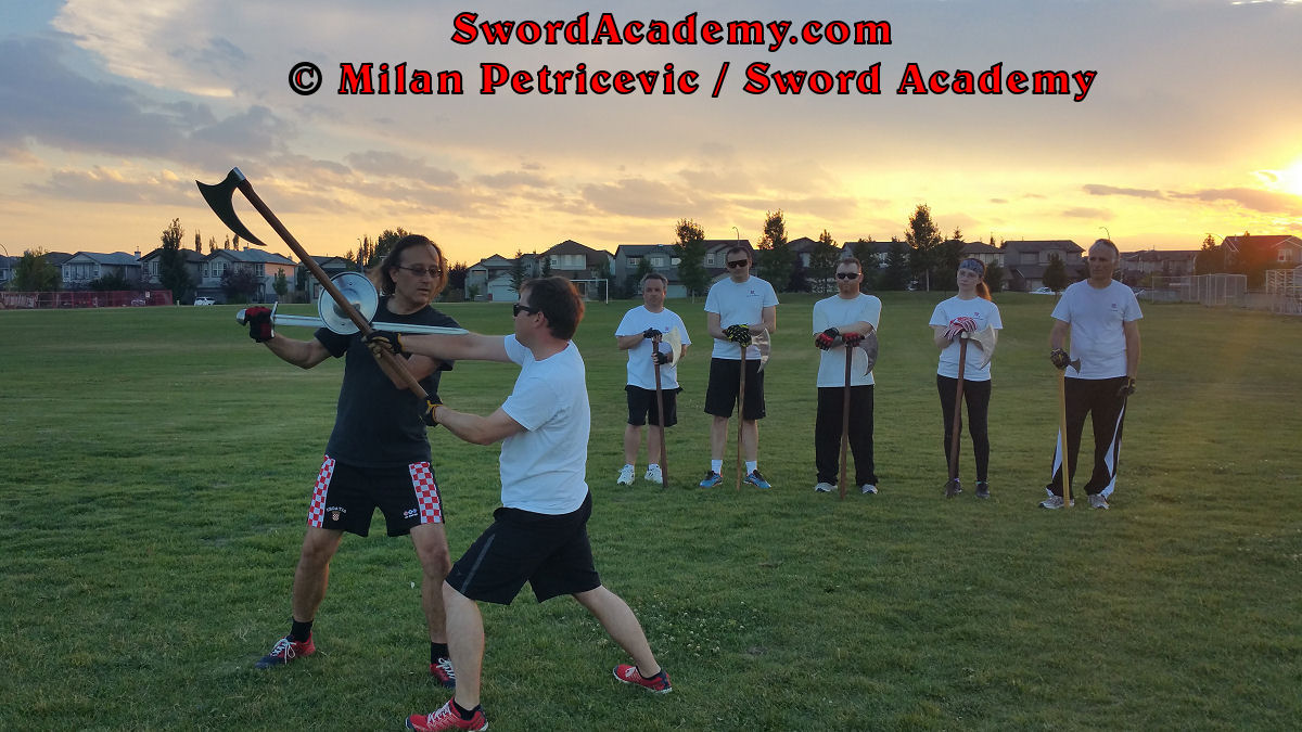 Milan demonstrates during an outdoor class in front of Sword Academy students defending with sword and buckler against the two handed axe attack exercise counter-striking and thrusting with the sword, while maintaining pressure with buckler as inspired by historical sources from the German medieval (and renaissance) tradition, part of Sword Academy HEMA / WMA / Martial Arts curriculum.
