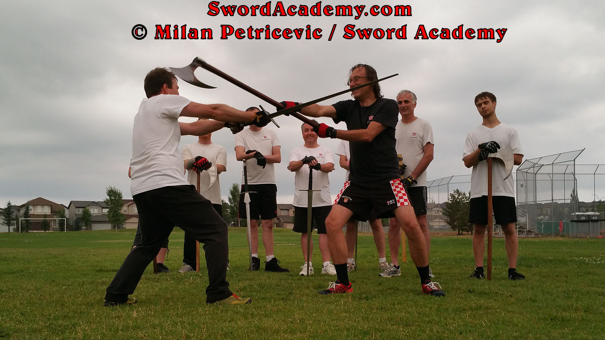 Milan demonstrates during an outdoor class in front of Sword Academy students two handed axe attack against the longsword exercise attacking from both sides as inspired by historical sources from the German medieval (and renaissance) tradition, part of Sword Academy HEMA / WMA / Martial Arts curriculum.